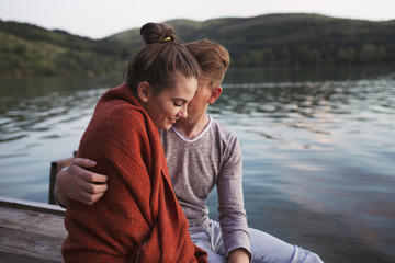 Couple wrapped in blanket sitting by the lake