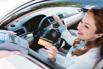 smiling businesswoman in car making payment with credit card