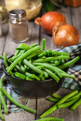 Raw green beans in a black dish