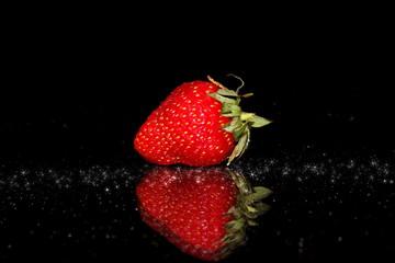 красивая красная клубника на черном фоне с отражением и бликами