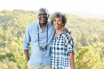 Portrait of African American Senior couple with a vintage film camera laughing outdoors