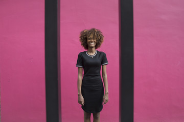 Young black woman in front of a purple wall.