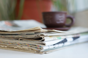 Newspapers and cup of tea, side view