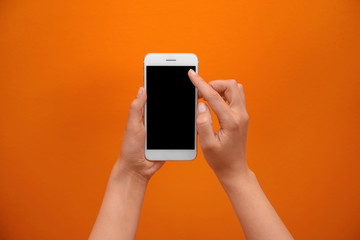Young woman holding mobile phone with blank screen in hand on color background
