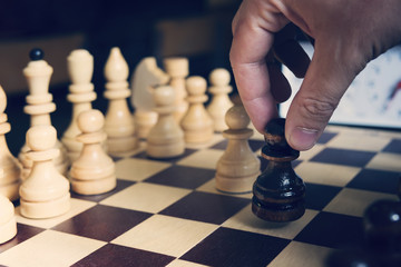 male hand playing chess on light blurred background. black pawn in the hand of the beginning of a game of chess