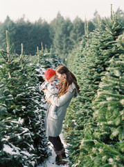 mom holds daughter at christmas tree farm