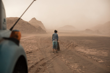 woman carrying sand ladders in the desert during sand storm