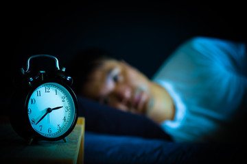 asian man in bed suffering insomnia and sleep disorder thinking about his problem at night