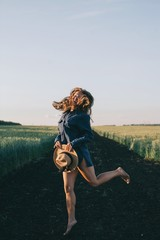 Emotional portrait of young female with long hair jumping and laughing in sunset light outdoors