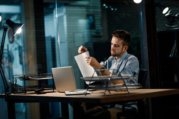 Casual man working in office sitting at table in lamplight and attaching paper heap with clip