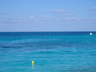 Panorama of turquoise waters of Caribbean Sea landscape with yellow bouyes and horizon line at Cancun city in Mexico