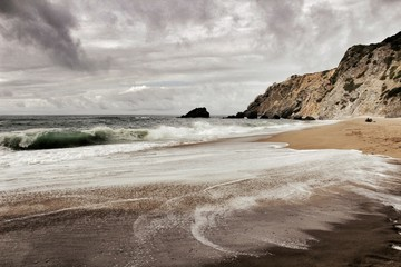 Brave ocean, rock formations and cloudy drama sky on the beach