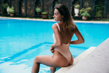 Rear view, charming girl in a swimsuit with a beautiful sports figure sitting near the swimming pool and enjoying the rest. Incredible young model with a sexy tanned body in a bikini.