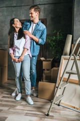 smiling young couple with boxes moving into new home