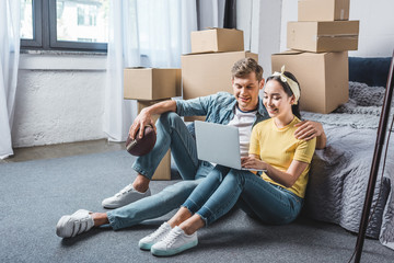 happy young couple sitting on floor of bedroom and using laptop while moving into new home