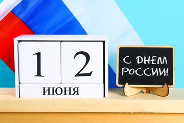 The inscription is June 12, the Day of Russia. Wooden white calendar on the background of the flag of Russia.