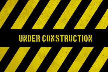 Under construction warning sign with yellow and black stripes painted over concrete wall coarse facade as texture background. Concept for do not enter the area, caution, danger, construction site.