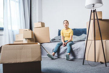 tired young woman surrounded with boxes relaxing on bed after relocation