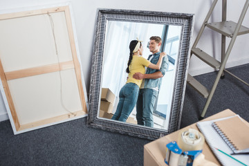 mirror reflection of young couple embracing after moving into new home
