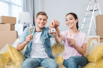 happy young couple with glasses of champagne and keys sitting on couch after relocation into new home