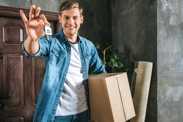 handsome smiling man with box and key moving into new home