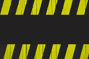 Warning sign with yellow and black stripes painted over cracked wood as border frame with black empty background space for text in the center of the frame.