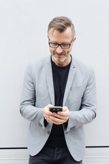 Mature man in grey jacket using mobile phone