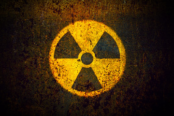 Round yellow radioactive (ionizing radiation) danger symbol painted on a massive rusty metal wall with dark rustic grungy texture background with vignetting. Wall mural