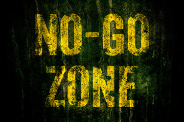 """""""No-Go Zone"""" warning sign in yellow letters painted over dark grungy concrete wall with moss. Sign as concept for: do not enter the area, caution, danger or off limits in violent urban areas"""