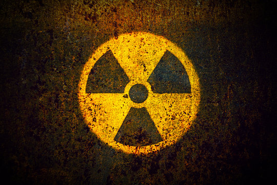 Round yellow radioactive (ionizing radiation) danger symbol painted on a massive rusty metal wall with dark rustic grungy texture background with vignetting.
