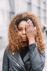 Pretty young African woman covering one eye