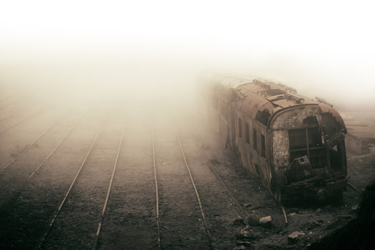 Abandoned rusting train and empty train tracks photographed in misty foggy day in the village Paranapiacaba, Sao Paulo, Brazil. Photo color toned with sepia for surreal and vintage nostalgic look.