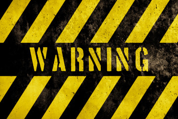 Warning sign text with yellow and dark stripes painted over concrete wall facade texture background. Concept image for caution, danger and hazard.