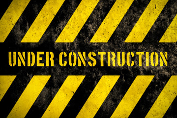 Under construction warning sign with yellow and dark stripes painted over concrete wall coarse facade as texture background. Concept for do not enter the area, caution, danger, construction site.