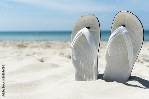 ee781a685 Flip flops in the sand on sea beach background
