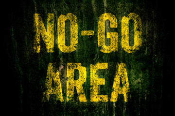 """""""No-Go Area"""" warning sign in yellow letters painted over dark grungy concrete wall with moss. Sign as concept for: do not enter the area, caution, danger or off limits in violent urban areas."""