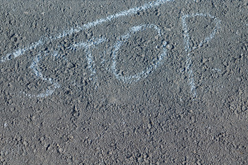 On the surface of the pavement or asphalt written word stop chalk and top line. The line and the word mean stop. It's a sign or a symbol. Restriction or prohibition. Asphalt is rough.