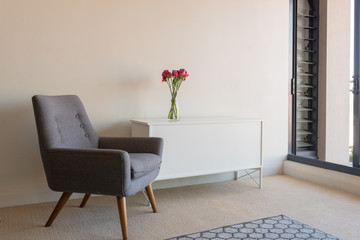 View of living room with retro grey armchair and white sideboard with red roses (selective focus)