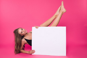 In a mood of total nudity! Attractive cheerful well-graced lady pleasantly smiling, while holding up her legs, while sitting on the floor with white board.