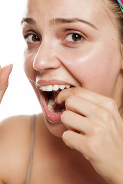 young woman cleans her teeth with a dental floss