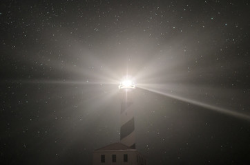 Landscape photograph of a Menorca lighthouse at night giving light and stars in the background.