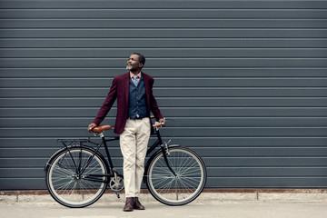 fashionable african american man in trendy jacket posing near bicycle Fotoväggar