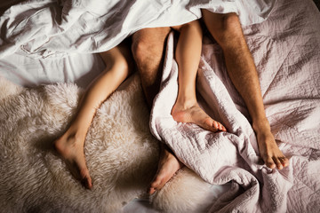 Legs of a couple in bed