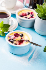Aluminium Prints Grocery Berry clafouti. Traditional french sweet fruit dessert clafoutis with raspberries and blueberries on blue background. Healthy gluten free food concept with copy space.