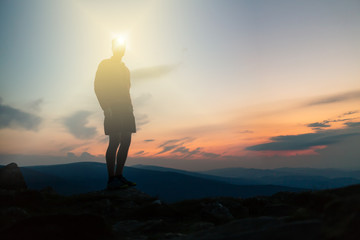 Man celebrating sunset looking at view in mountains Wall mural