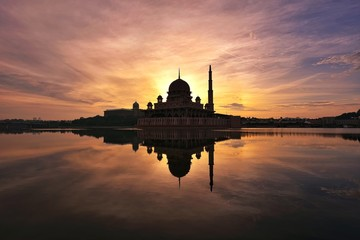 Wall Mural - Reflections of silhouette mosque during sunrise