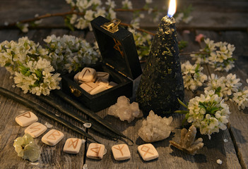 Black candles with old runes, crystals and flowers on planks. Occult, esoteric and divination still life. Halloween background with vintage objects