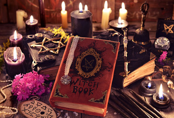 Witch books, black candles with magic and mystic objects on planks. Occult, esoteric and divination still life. Halloween background with vintage objects