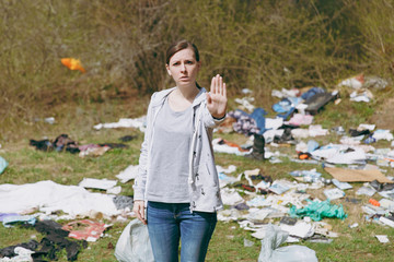 Young upset concerned woman in casual clothes cleaning showing stop gesture with palm in littered park. Problem of environmental pollution. Stop nature garbage, environment protection concept.
