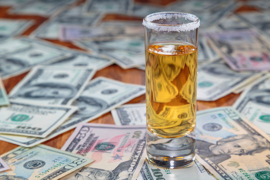 tequila gold on a background of randomly laid out the American dollars of different face value.